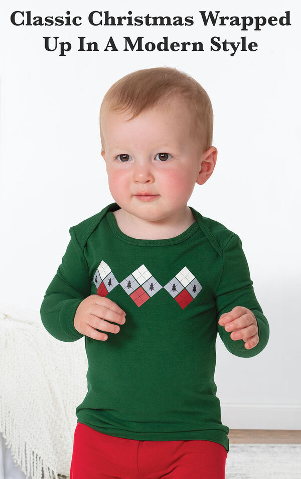 Model standing by bed wearing Holiday Argyle Pajamas with the following copy: Classic Christmas Wrapped Up in a Modern Style image number 2