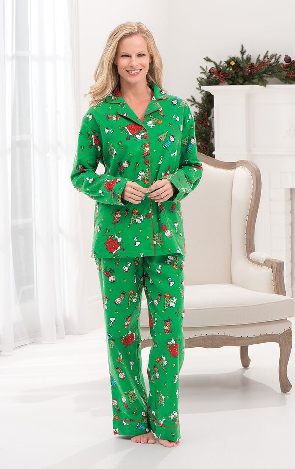 Model standing by chair wearing Green with Red Trim Charlie Brown Christmas Women's Pajamas image number 3