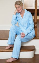 Model sitting on stairs wearing light blue button-up pajamas with white polka dots image number 2