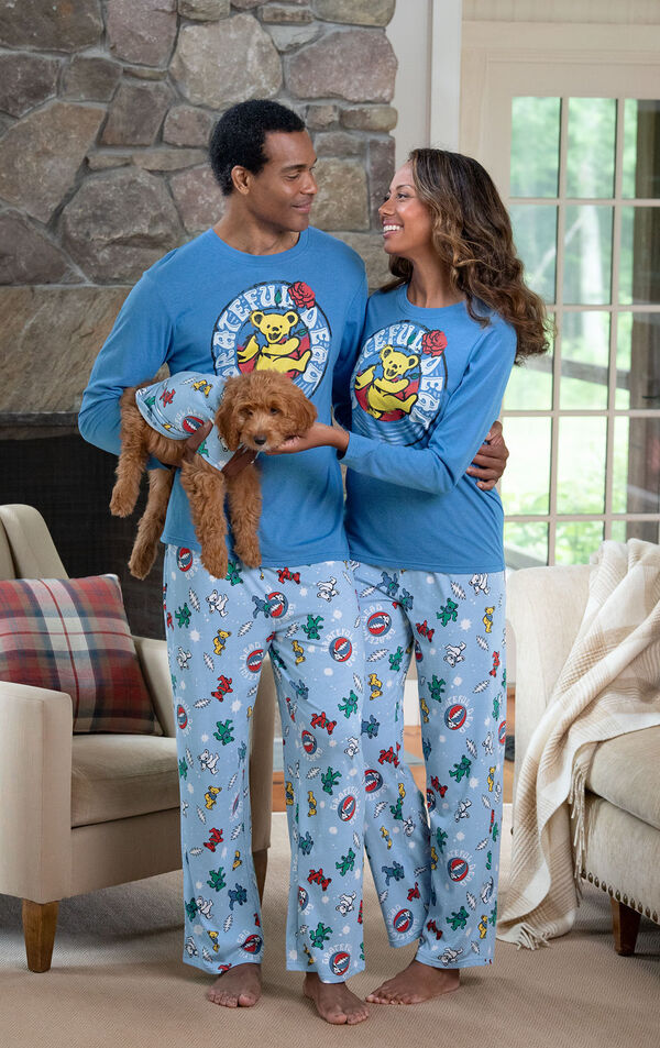Woman and Man in front of the fireplace holding their dog, all wearing matching Grateful Dead Pajamas image number 1