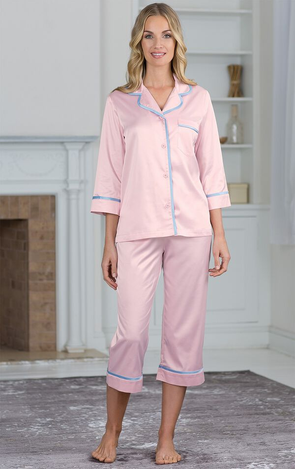 Model standing by fireplace wearing Light Pink with Blue trim Dreamy Satin Capri Pajamas image number 3