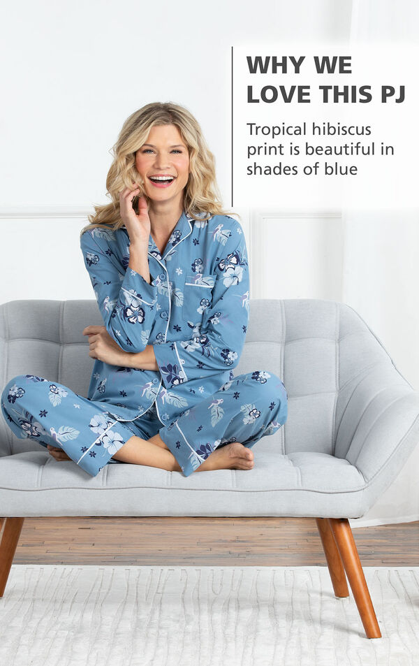 Model sitting cross legged wearing Margaritaville Blue Hibiscus Print PJs with White Trim and the following copy: Tropical hibiscus print is beautiful in shades of blue image number 2