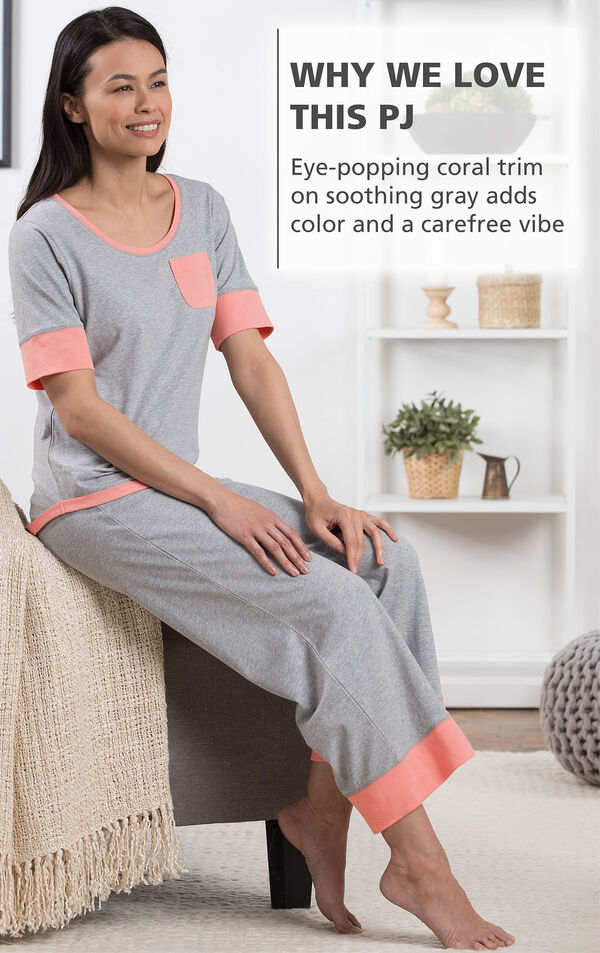 Model sitting wearing Cozy Capri Pajama Set with the following copy: Why We Love This PJ - eye-popping coral trim on soothing gray adds color and carefree vibe image number 3