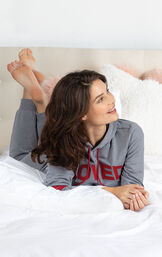 Model laying down on bed wearing Gray and Red 'Loved'' Hoodie Pajamas image number 2
