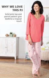 Model by bed wearing Margaritaville Tropical Dreams Pajamas - Pink with the following copy: Solid pink top and parrot pattern give bedtime a tropical touch image number 3