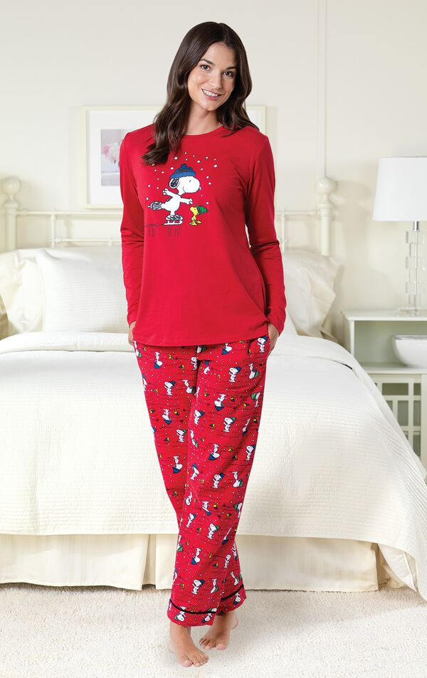 Model by bed wearing Red Snoopy and Woodstock Women's Pajamas image number 1