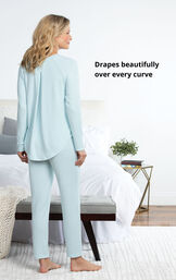 Model standing by bed wearing Blue Cloud Fine Pajamas with the following copy: Drapes beautifully over every curve image number 4