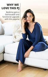 Model sitting on couch wearing Navy Blue Jumpsuit PJs with the following copy: Bedtime gets a fashionable and functional upgrade with this pajama image number 3