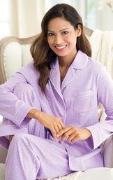 Model sitting in chair wearing light purple button-up pajamas with white polka dots image number 2