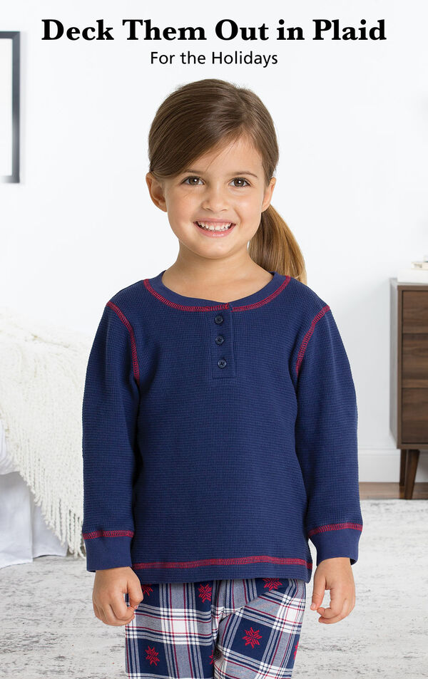 Toddler girl wearing Snowfall Plaid Toddler Pajamas by bed with the following copy: Deck Them Out in Plaid for the Holidays. image number 1