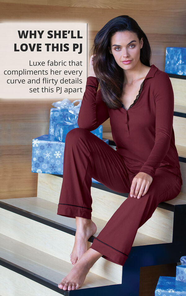 Model sitting on couch wearing Midnight Fantasy Pajamas - Black with the following copy: Luxe fabric that compliments her every curve and flirty details set this PJ apart image number 2