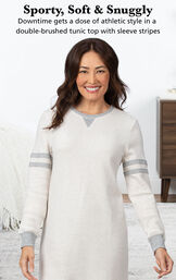 Model wearing Sporty Sweatshirt and Leggings PJ Set - Ivory/Gray by bed with the following copy: Sporty, Soft and Snuggly. Downtime gets a dose of athletic style in a double-brushed tunic top with sleeve stripes. image number 2
