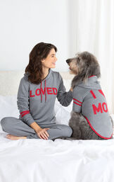 """Woman and dog sitting on Bed wearing matching Gray hoodie Pajamas - Woman's says """"Loved"""" on the hoodie and dog's says """"I Heart Mom"""" image number 1"""