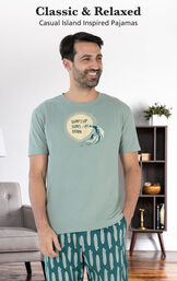 Model wearing Margaritaville Summer Breeze Men's Pajamas - Teal by couch with the following copy: Casual Island Inspired Pajamas image number 2