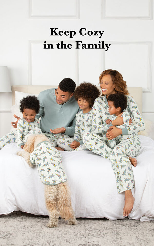 Family sitting on bed wearing Sage Green and White Balsam and Pine Matching Family Pajamas, with the following copy: Keep Cozy in the Family image number 1