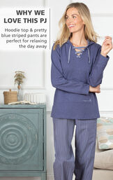 Model standing by couch wearing Margaritaville Cool Nights Hoodie Pajamas - Navy with the following copy: Hoodie top and pretty blue striped pants are perfect for relaxing the day away image number 2