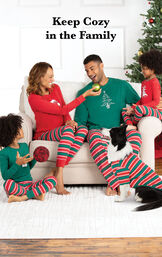 Family sitting by Christmas Tree wearing Red and Green Christmas Stripe Matching Family Pajamas with the following copy: Keep Cozy in the Family image number 1