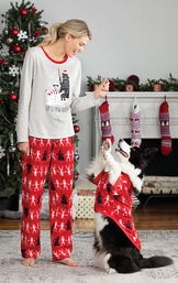 Woman standing in front of fireplace wearing Red Star Wars PJs, playing with dog who is wearing Matching Red Star Wars PJs. image number 1