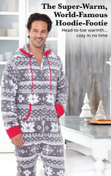 Model wearing Hoodie-Footie™ for Men - Nordic Fleece by a table with the following copy: The Super-Warm, World-Famous Hoodie-Footie - Head-to-toe warmth, cozy in no time image number 1