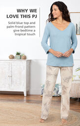 Model by bed wearing Margaritaville Pajamas - a solid blue 3/4 sleeve top with full-length pants in a cream palm-frond pattern that gives bedtime a tropical touch image number 2