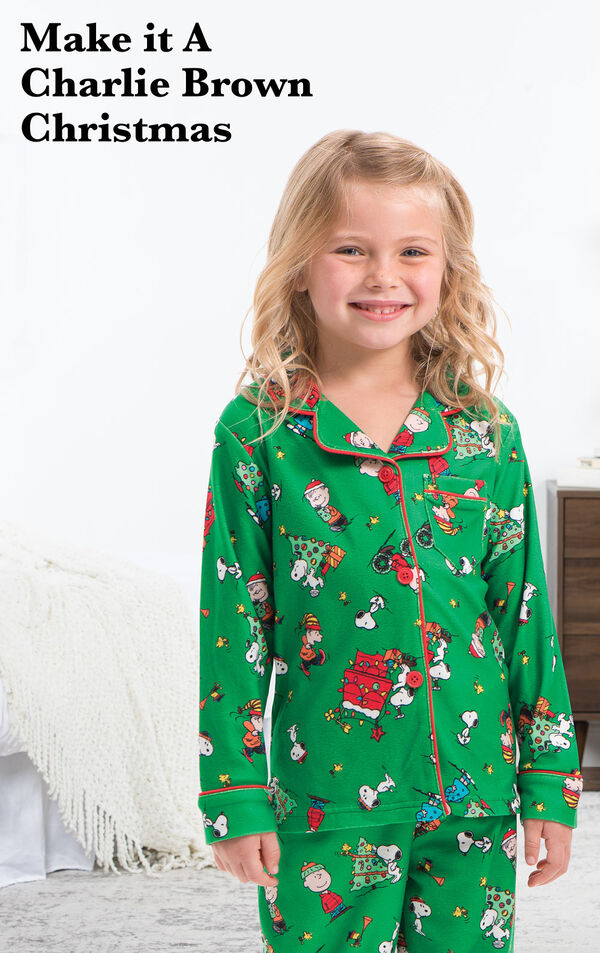 Toddler wearing Charlie Brown Christmas Pajamas by bed with the following copy: Make it a Charlie Brown Christmas. image number 1