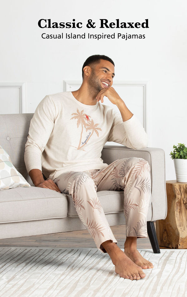 Model sitting on couch wearing Tan Margaritaville Easy Island Men's Pajamas with the following copy: Classic and Relaxed - Casual Island Inspired Pajamas image number 2