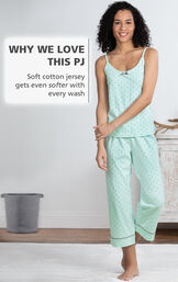 Model standing by bed wearing Mint Polka-Dot Cami and Capri Pajamas with the following copy: Soft cotton jersey gets even softer with every wash image number 3