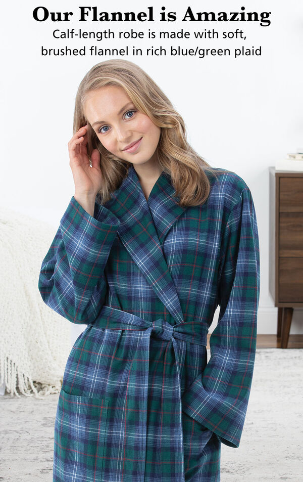Model wearing Heritage Plaid Flannel Long Robe by bed with the following copy: Our Flannel is Amazing. Calf-length robe is made with soft, brushed flannel in rich blue/green plaid image number 2