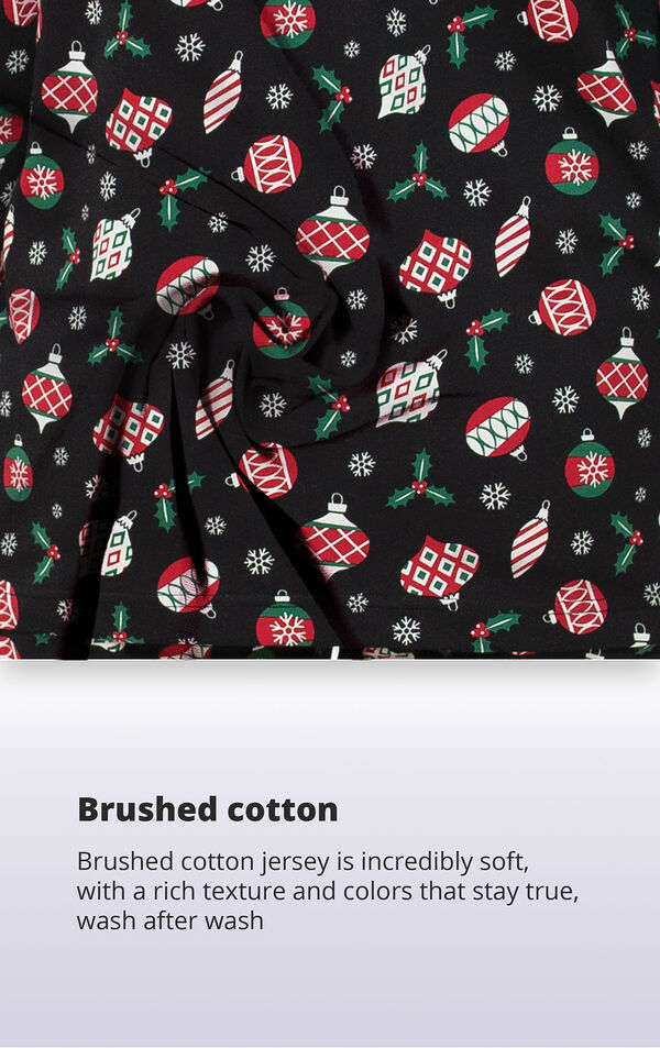 Black fabric with christmas ornament print with the following copy: brushed cotton jersey is incredibly soft, with a rich texture and colors that stay true image number 4