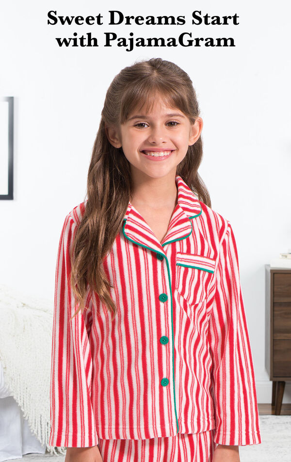 Girl wearing Candy Cane Fleece Girls Pajamas by bed with the following copy: Sweet Dreams Start with PajamaGram. image number 1
