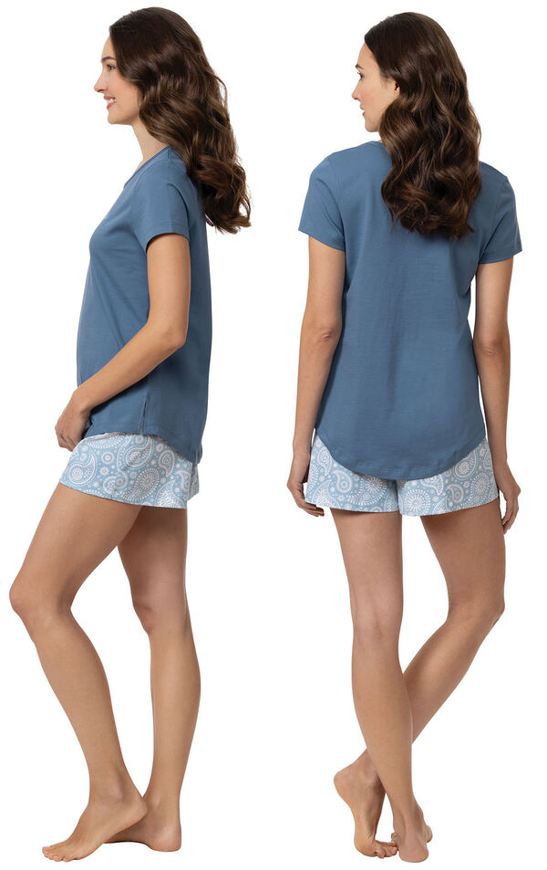 """Model wearing blue short sleeve shirt with """"let me sleep"""" text and matching blue and white paisley print shorts, facing away from the camera and then facing to the side image number 1"""