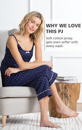 Model sitting on couch wearing Polka-Dot Cami and Capri Pajamas - Navy with the following copy: Soft cotton jersey gets even softer with every wash image number 2