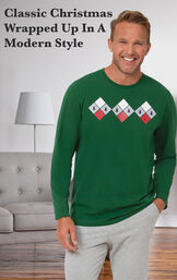 Model standing by couch wearing Green and Gray Holiday Argyle Men's Pajamas with the following copy: classic christmas wrapped up in a modern style image number 2