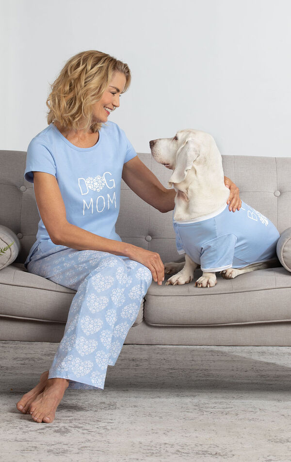 Model wearing Dog Mom PJs sitting on couch petting Dog wearing Fur Baby PJs image number 1