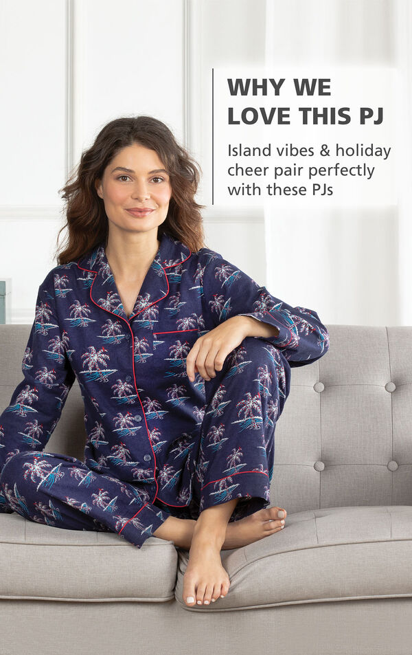 Model sitting on couch wearing Margaritaville Flannel Boyfriend Pajamas - Christmas Palm Trees print with the following copy: Island vibes and holiday cheer pair perfectly with these PJs image number 2