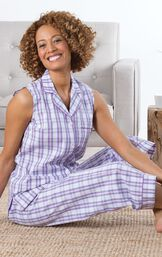 Model sitting by couch wearing Purple and White Perfectly Plaid Sleeveless Capri Pajamas image number 3
