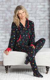 Model sitting on ottoman wearing a black fleece with multicolored stars Hoodie-Footie onesie image number 1