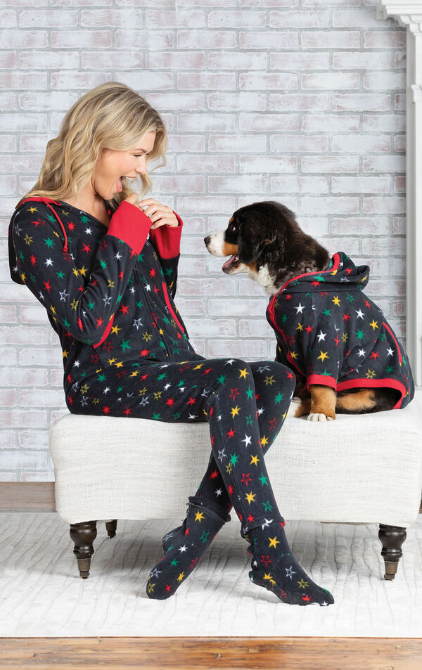 Woman and dog sitting on Ottoman wearing matching Fleece Onesie Hoodie-Footies - Black with multicolored stars image number 2