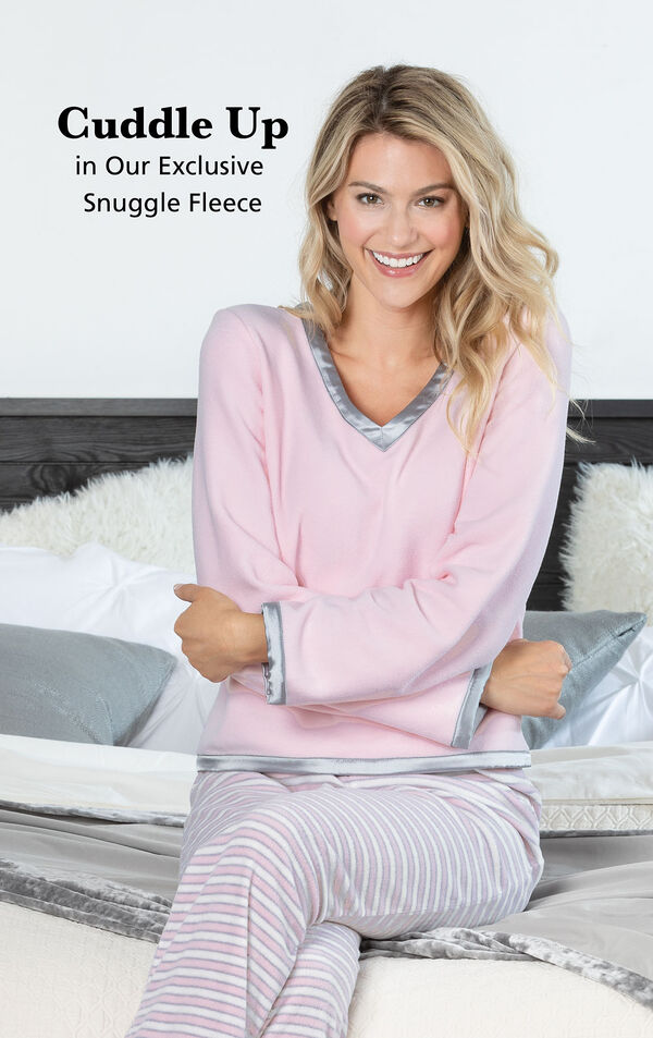 Model wearing Snuggle Fleece Pajamas - Pink Stripe by couch with the following copy: Cuddle Up in our exclusive snuggle fleece. image number 2