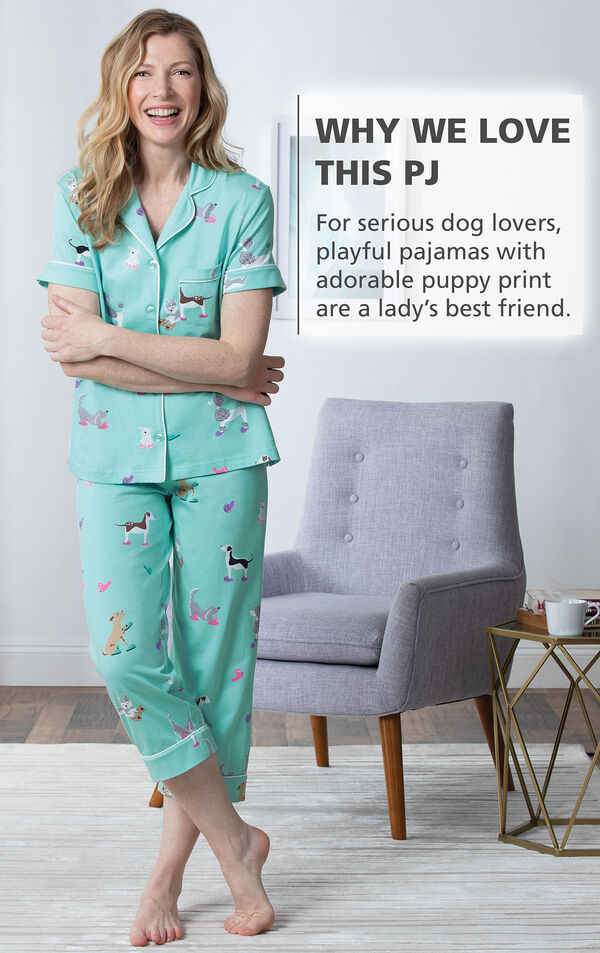 Model standing by chair wearing Light Blue Dog Print Short Sleeve Button-Front Capri PJ for Women with the following copy: For serious dog lovers, playful pajamas with adorable puppy print are a lady's best friend image number 2