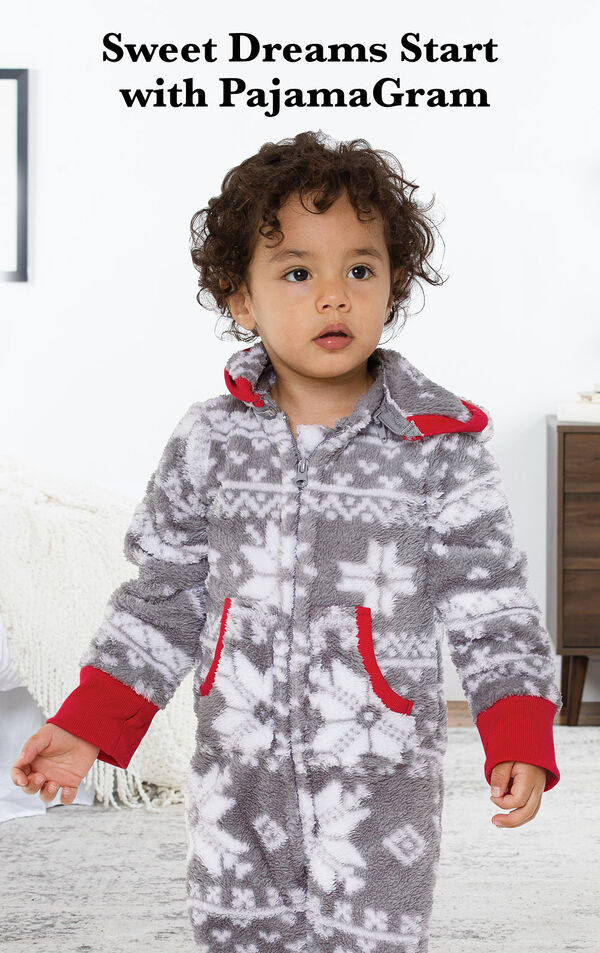 Toddler wearing Nordic Fleece Hoodie-Footie by bed with the following copy: Sweet Dreams Start with PajamaGram. image number 1