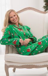 Model sitting on chair wearing Green with Red Trim Charlie Brown Christmas Women's Pajamas image number 4