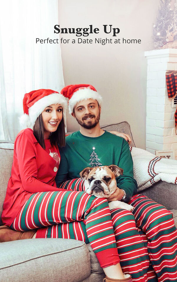 Couple sitting on the couch wearing matching Christmas Stripe Pajamas with the following copy: Snuggle Up - Perfect for a Date Night at Home image number 1