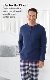 Model wearing Snowfall Plaid Men's Pajamas by a bed with the following copy: Perfectly Plaid. 2-piece thermal PJs stand out with plaid on soft, warm cotton pants image number 1