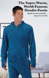 Model wearing Hoodie Footie™ for Men - Blue by chair with the following copy: The Super-Warm, World-Famous Hoodie-Footie - Head-to-toe warmth, cozy in no time image number 1