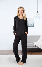 Model wearing Black Tie-Neck PJ for Women, standing by couch image number 2