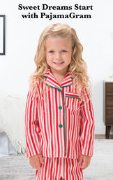 Toddler girl wearing Candy Cane Fleece Pajamas by bed with the following copy: Sweet Dreams Start with PajamaGram. image number 1