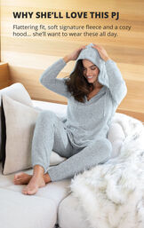 Model sitting on bed wearing Cozy Escape Pajamas with the hood up and the following copy: Why She'll Love this PJ: Flattering fit, soft signature fleece and a cozy hood, she'll want to wear these all day image number 3