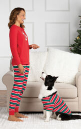 Woman standing in front of couch wearing Red and Green Christmas Stripe PJs, playing with dog who is wearing matching pajamas image number 1