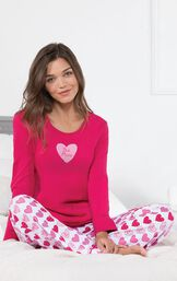 Model sitting on bed wearing Pink and White Be Mine Heart Print Pajamas image number 3